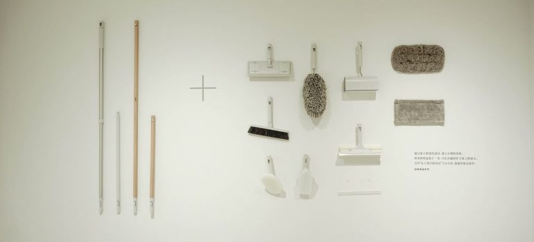 various cleaning tools on a white wall