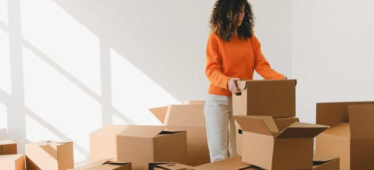 a woman in an orange sweater packing cardboard boxes