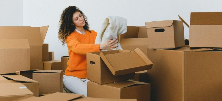 a woman in an orange sweater packing winter clothes in cardboard boxes