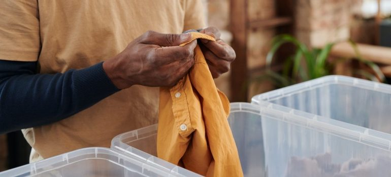 Man and plastic boxes ready to declutter your home in 5 days