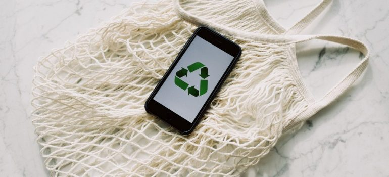 Recycle symbol on a smartphone on a bag