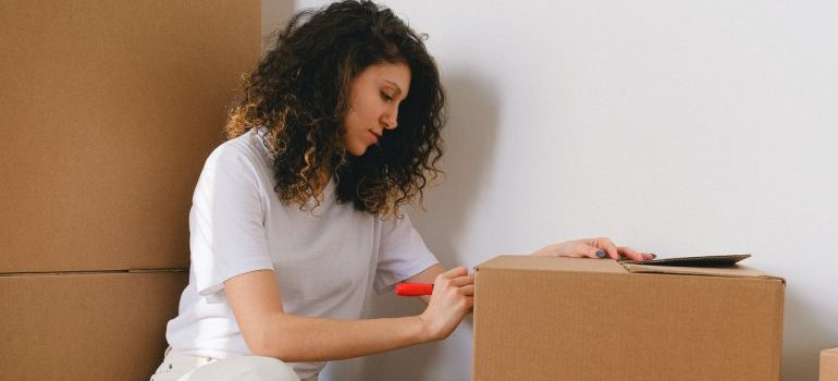 woman labeling box to avoid mistakes people make when packing
