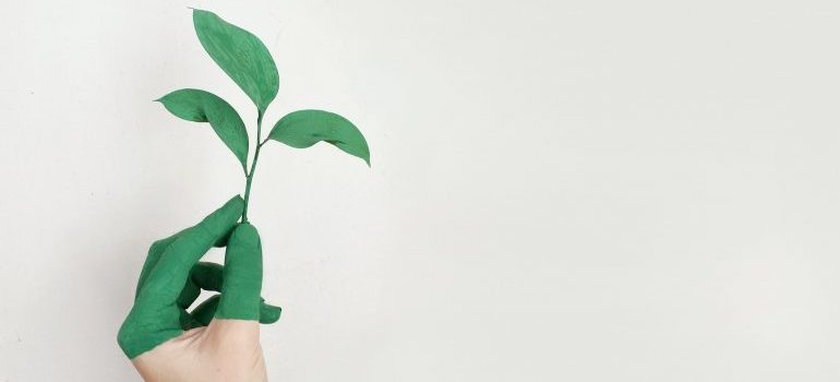 A hand painted in green holding a leaf